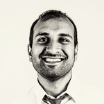 Black and white passport picture of Sujan Patel in a broad smile